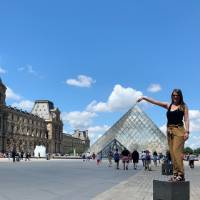 Student posing in front of the Louvre